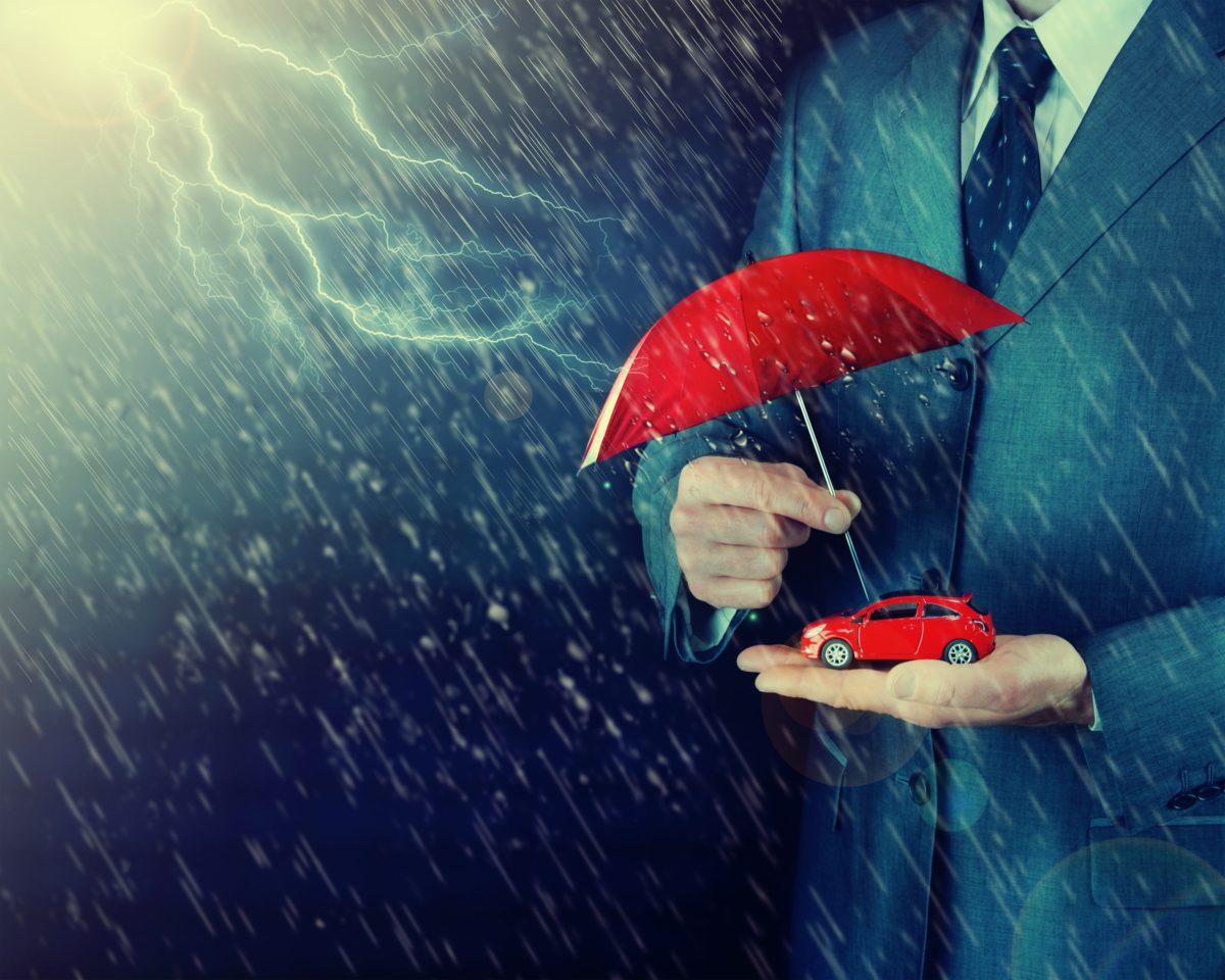 persona sosteniendo auto con paraguas